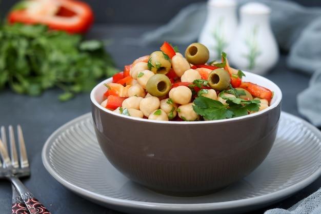 Salada saudável de grão de bico, azeitonas verdes, pimenta e salsa, está localizada em uma superfície escura