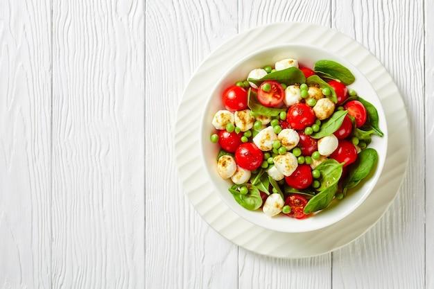 Salada saudável de mini bolas de mussarela, tomate cereja fresco de espinafre e ervilhas jovens com molho de vinagre balsâmico em um prato branco sobre uma mesa de madeira branca, vista de cima, espaço de cópia