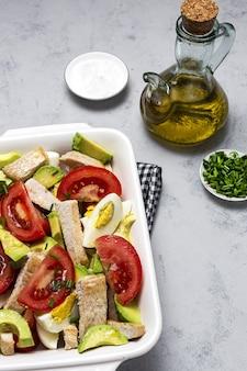 Salada saudável de ovo, frango, abacate e tomate com azeite de oliva