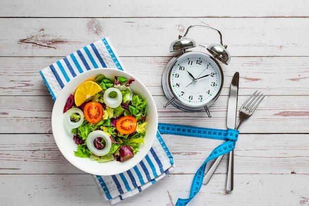 Salada saudável e despertador, isolado em fundo de madeira.