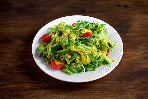 Salada saudável e dietética com abacate, sementes de gergelim, molho amarelo e tomate cereja, servida em um prato branco sobre uma superfície de madeira