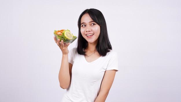 Salada saudável e feliz jovem asiática com superfície branca isolada.