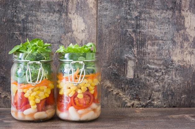 Salada saudável em frasco de vidro com feijão branco, tomate, cebola, milho e alface na mesa de madeira