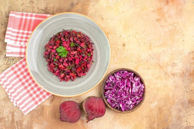 Salada saudável vermelha de vista superior vestida com folhas de salsa feitas de beterraba e tigela de repolho picado em um fundo de madeira com local de cópia