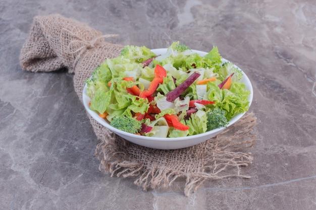 Salada simples feita de folhas de repolho picadas, cenoura, pimentão, beterraba, cebola e brócolis em superfície de mármore
