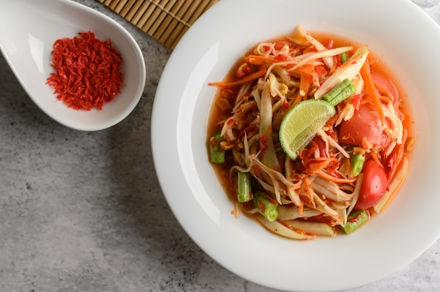 Salada tailandesa de mamão em um prato branco e camarão seco