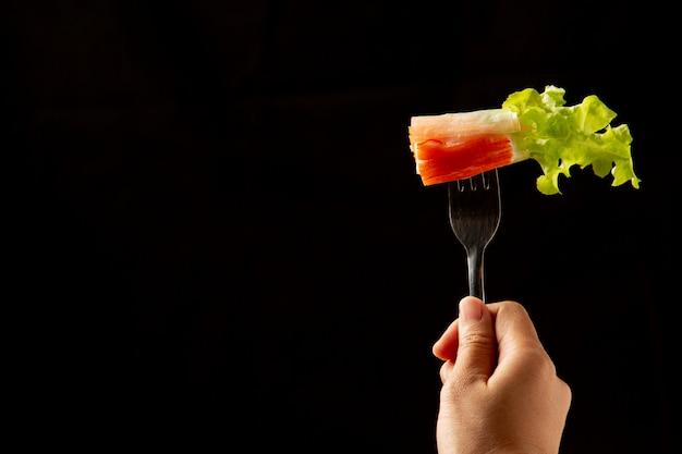 Salada tailandesa garlicky em talheres na mão