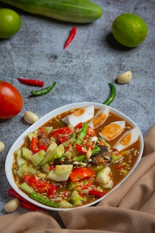 Salada tailandesa picante com pepinos e pimentas em ovos salgados.