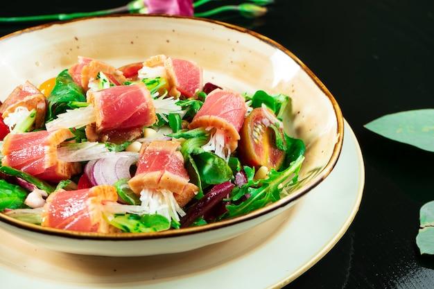 Salada tataki fresca e deliciosa com atum, alface, cebola roxa, tomate cereja e rabanete daikon. salada de frutos do mar saborosos da culinária japonesa em tigela amarela sobre fundo escuro.