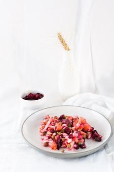 Salada tradicional russa com legumes - vinagrete em um prato e uma tigela de beterraba em uma mesa em um pano. visão vertical