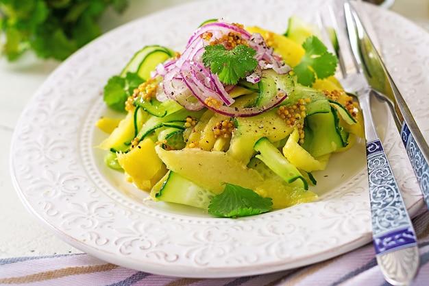 Salada vegan saudável manga, pepino, coentro e cebola vermelha em molho agridoce. comida tailandesa. refeição saudável.