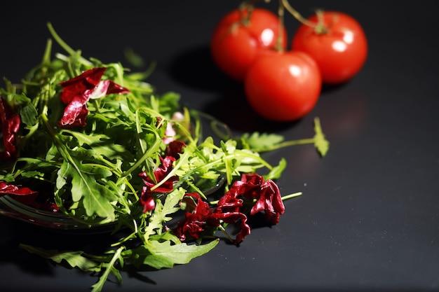 Salada vegana verde com mistura de folhas verdes e vegetais. folhas frescas de rúcula em uma peneira. fundo preto.