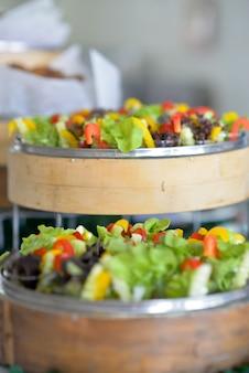 Salada vegetal preparada em um recipiente para uma festa.