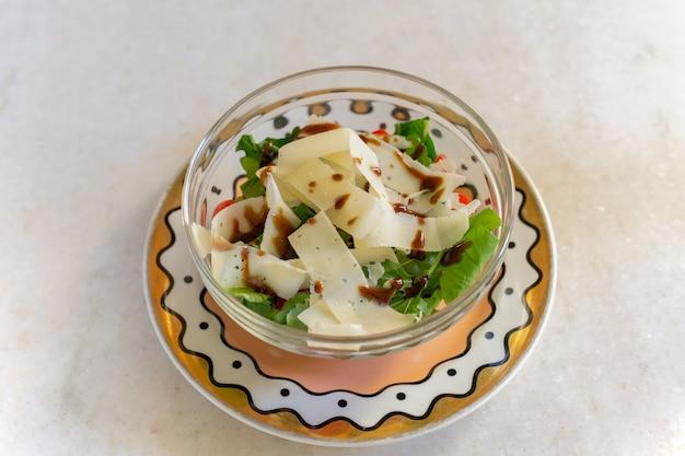 Salada vegetal verde com fatia de queijo parmesão na bacia de vidro.