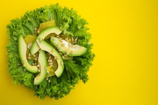 Salada vegetariana com abacate, folhas de alface, laranja e pinhões no fundo amarelo.