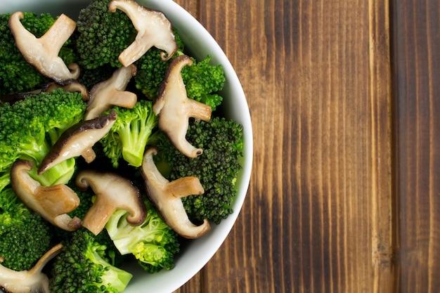 Salada vegetariana com cogumelos shiitake e brócolis na tigela branca sobre o fundo de madeira marrom