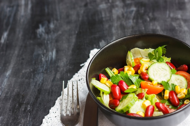 Salada vegetariana com feijão vermelho, milho, rúcula, tomate cereja e azeite