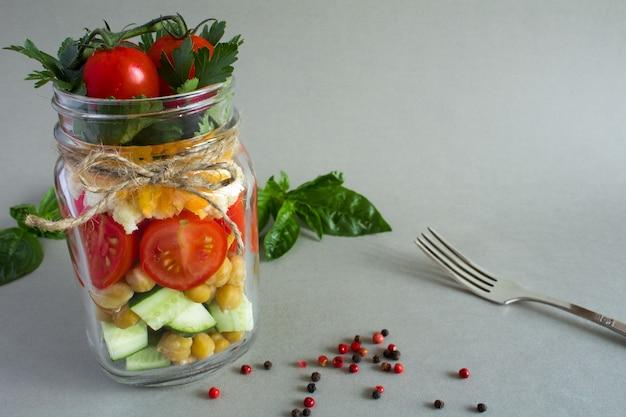 Salada vegetariana com legumes e grão de bico na jarra de vidro na superfície cinza