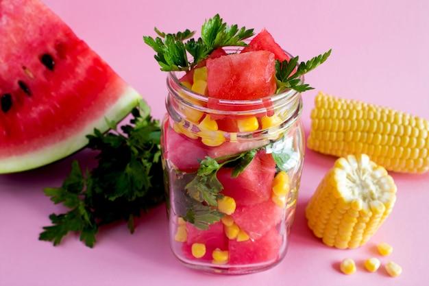 Salada vegetariana com melancia e milho na jarra de vidro no fundo rosa