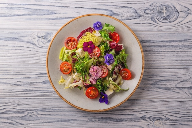 Salada vegetariana com tomate, alface e queijo decorado com flores comestíveis. conceito de comida de primavera.