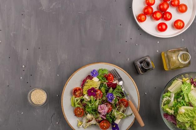 Salada vegetariana com tomate, alface e queijo decorado com flores comestíveis e ingredientes em uma mesa cinza. conceito de comida de primavera. fundo com espaço de cópia