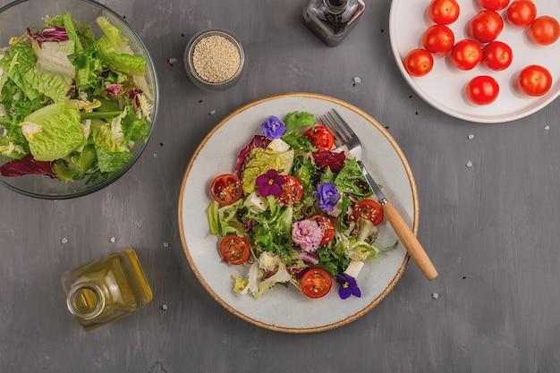 Salada vegetariana com tomate, alface e queijo decorado com flores comestíveis e ingredientes em uma mesa cinza. conceito de comida de primavera.