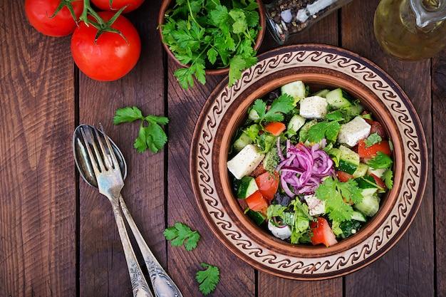 Salada vegetariana com tomate cereja, queijo brie, pepino, coentro e cebola vermelha. cozinha americana. vista do topo. configuração plana