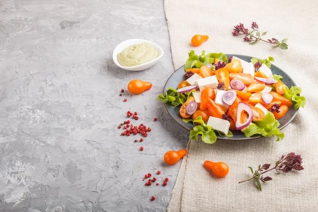 Salada vegetariana com tomates frescos de uva, queijo feta, alface e cebola, vista lateral.