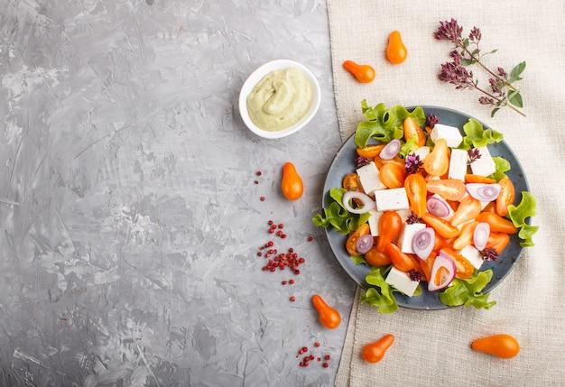 Salada vegetariana com tomates frescos de uva, queijo feta, alface e cebola, vista superior fundo