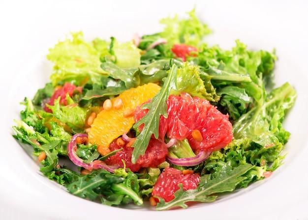 Salada vegetariana com toranja, laranja, pinhão e uma mistura de folhas de alface