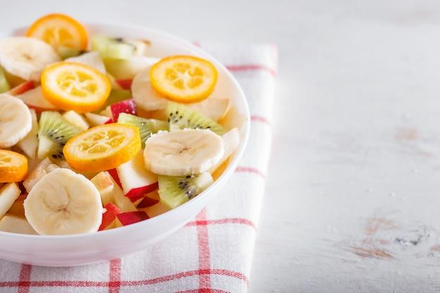 Salada vegetariana de bananas, maçãs, peras, kumquats e kiwi na toalha de mesa de linho