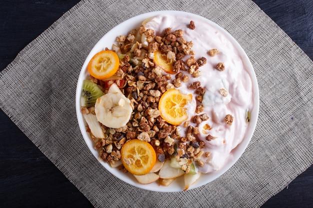 Salada vegetariana de bananas, maçãs, peras, kumquats, kiwi com granola e iogurte em fundo preto de madeira.