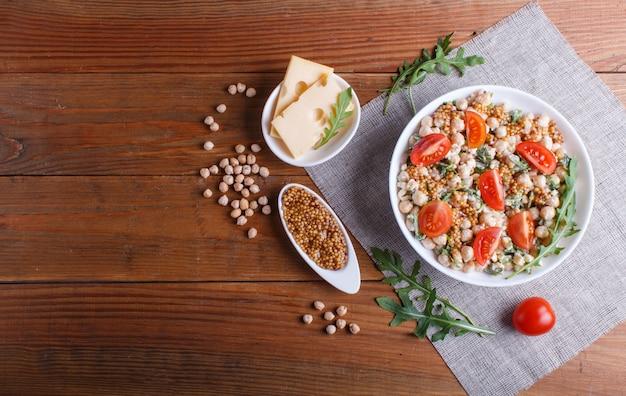Salada vegetariana de grão de bico cozido, queijo, rúcula, mostarda e tomate cereja