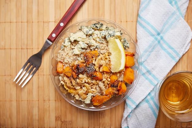 Salada vegetariana de queijo quiniam e nozes. acompanha, garfo e palito de fósforo. veja a sobrecarga. em madeira.