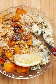 Salada vegetariana de queijo quiniam e nozes. veja a sobrecarga. em madeira.