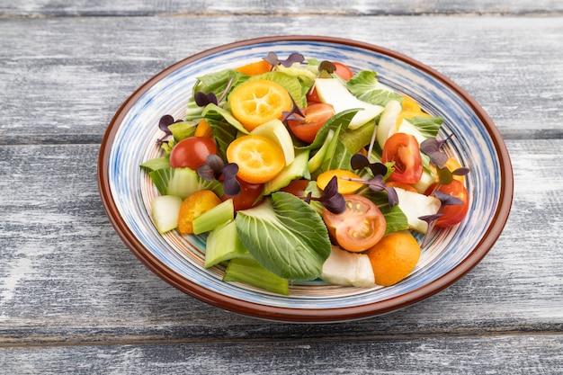 Salada vegetariana de repolho pac choi, kiwi, tomate, kumquat, brotos de microgreen