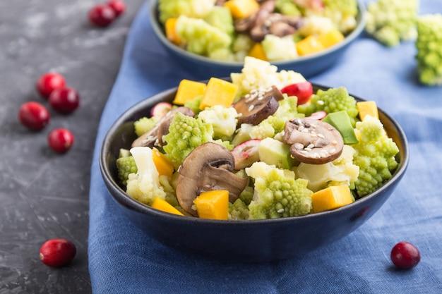 Salada vegetariana de repolho romanesco, champignon, cranberry, abacate e abóbora em um fundo preto de concreto. vista lateral, foco seletivo.