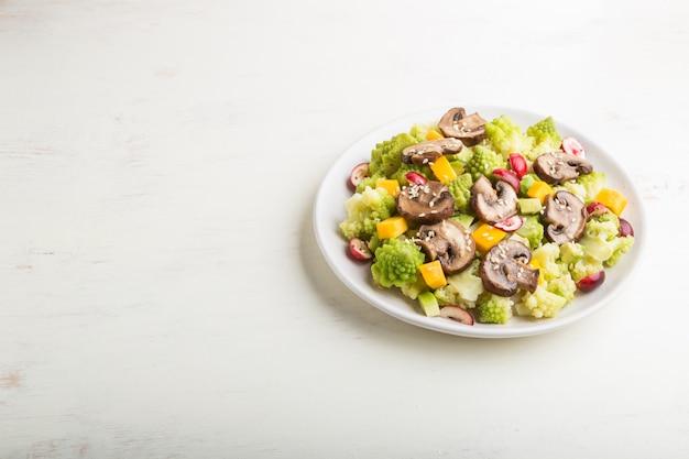 Salada vegetariana de repolho romanesco, champignon, cranberry, abacate e abóbora. vista lateral, copyspace.