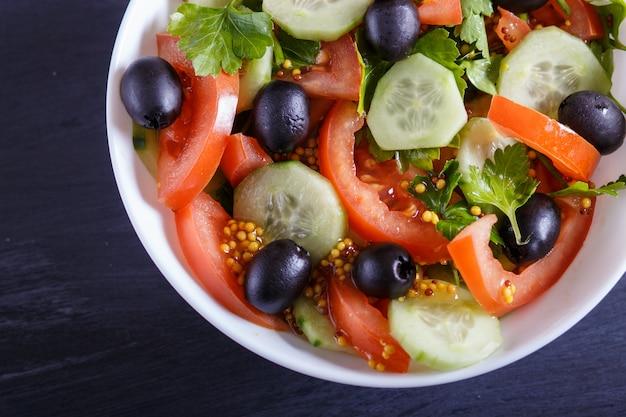 Salada vegetariana de tomates, pepinos, salsa, azeitonas e mostarda em fundo preto de madeira.