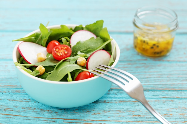 Salada vegetariana em tigela com molho de maracujá em frasco de vidro na mesa de madeira