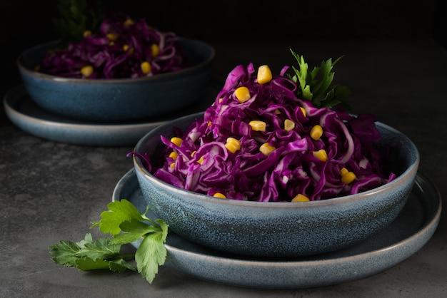 Salada vegetariana fresca com repolho roxo e milho em uma superfície cinza escura