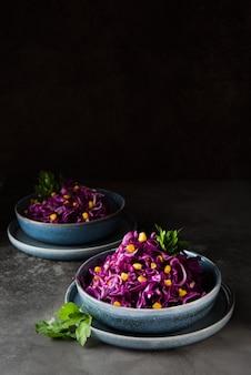 Salada vegetariana fresca com repolho roxo e milho em uma superfície cinza escuro, copie o espaço