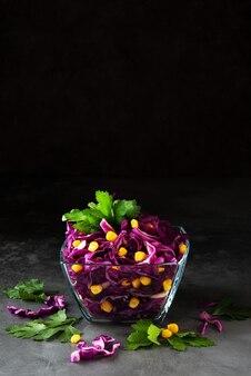 Salada vegetariana fresca com repolho roxo e milho em uma superfície escura, copie o espaço