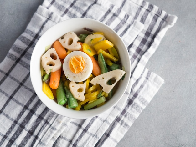 Salada vegetariana na tigela na mesa cinza