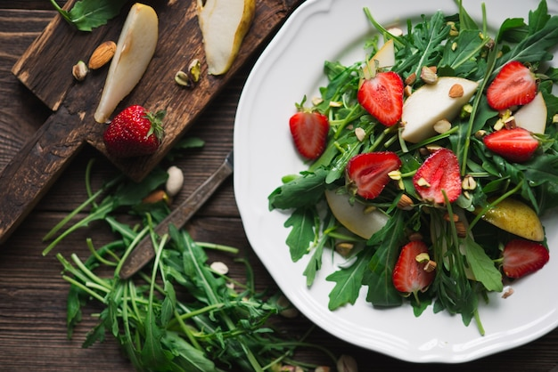 Salada vegetariana saudável com morango, rúcula, pêra e amêndoa