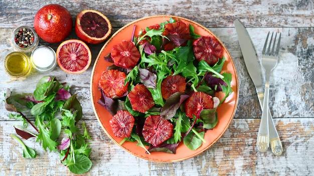 Salada vegetariana saudável da mistura com laranjas vermelhas.
