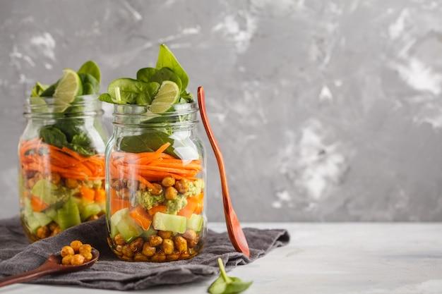Salada verde caseiro em um frasco de vidro com grão de bico cozido, guacamole e legumes, copie o espaço. conceito de comida vegan de desintoxicação de dieta saudável.