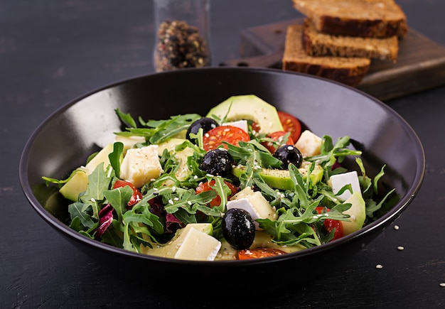 Salada verde com abacate fatiado, tomate cereja, azeitonas pretas e queijo.