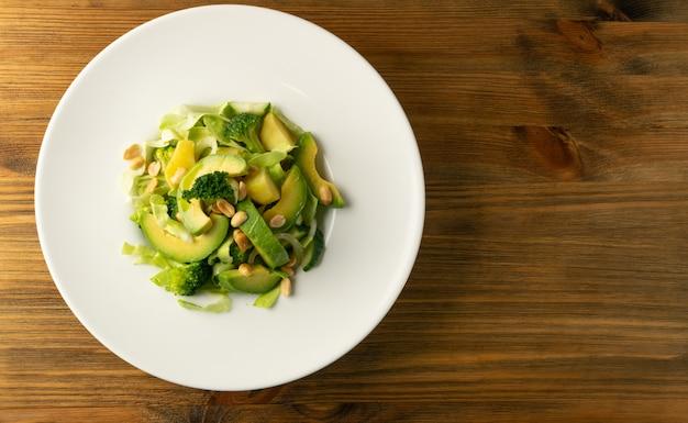Salada verde com abacate, pepino e nozes na chapa branca
