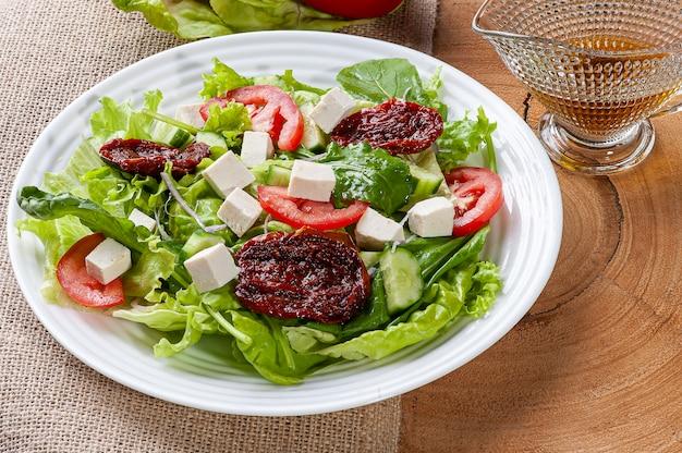 Salada verde com alface, rúcula, pepino, queijo e tomates secos